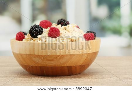 tasty oatmeal with berries, on table, on window background