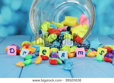 Scattered pieces of paper and colored stones with dreams in glass vase on blue wooden table on blue background