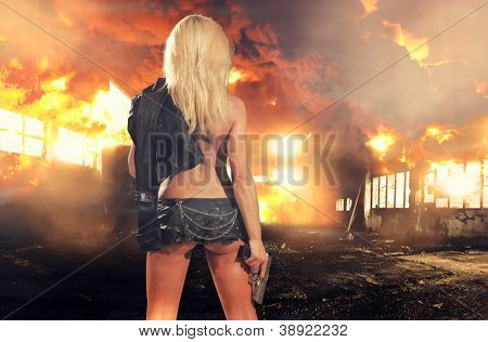 special tactics sexy woman holding up her weapon with explosion behind her