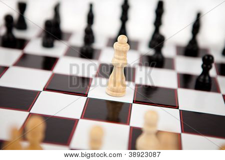 White queen standing the middle of the chessboard