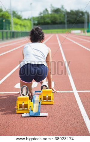Woman at starting blocks on track field