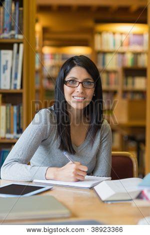 Mujer de pelo negro haciendo algunas investigaciones en la biblioteca