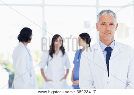 Serous doctor standing in the foreground and accompanied by his team