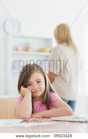 Little girl with paper and colouring pencils leaning on kitchen table with mother standing behind