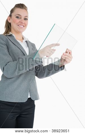 Businesswoman dialling on the glass slide while smiling