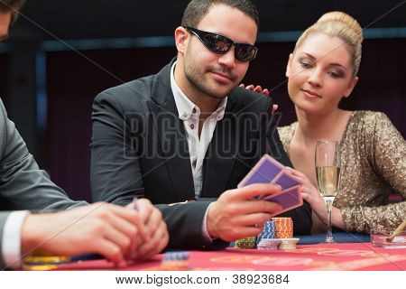Man in sunglasses showing hand to woman beside him at poker game in casino