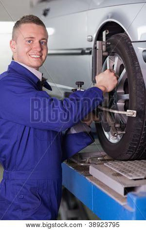 Smiling mechanic changing a car wheel in a garage