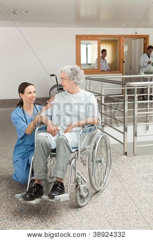 Nurse looking after old women sitting in wheelchair in hospital corridor