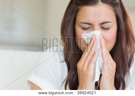 Burnette woman blowing nose into tissue