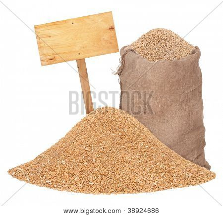 Heap of wheat grains with wooden price tag and sack