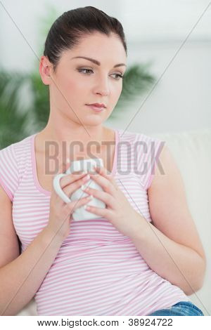 Thoughtfully woman sitting on the couch in a living room and holding a cup
