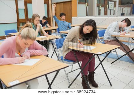 Students sitting at the classroom while student is raising hand to ask question