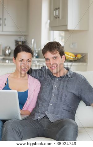 Young couple sitting on the couch in the living room and working on the laptop
