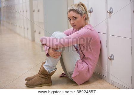 Upset girl sitting in hallway against lockers