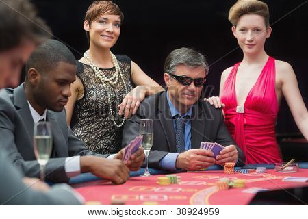 Man in sunglasses playing poker with two women either side in casino