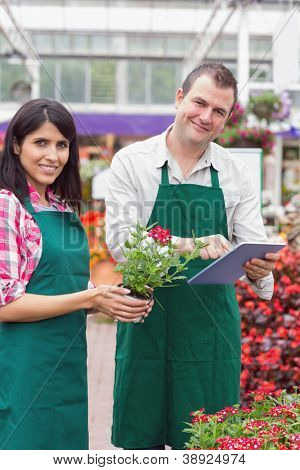 Happy workers using tablet pc and holding flower pot in garden center