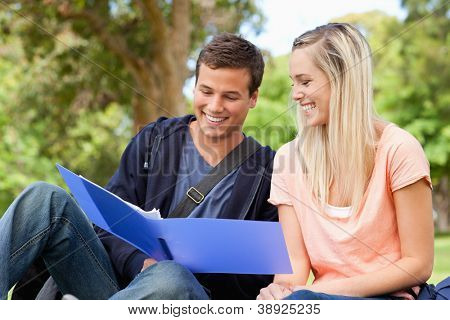 Close-up of a smiling tutor helping a teenager to revise in a park