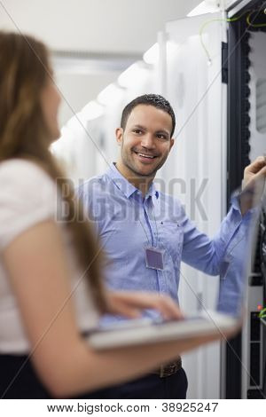 Technician smiling at colleauge holding laptop in data center
