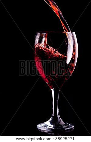 Red wine being poured into glass against black background