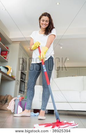 Woman mopping the floor of living room