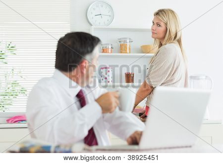 Wife looking disapprovingly at husband using laptop at breakfast in kitchen