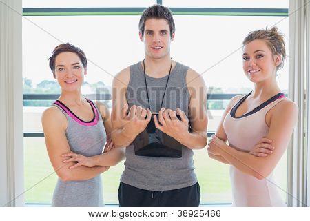 Trainer standing between two smiling women in fitness studio