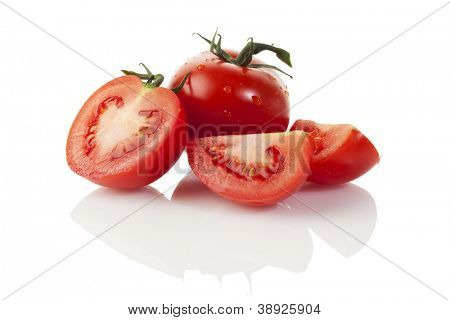 Whole and dissected tomatoes with water drops isolated on white background