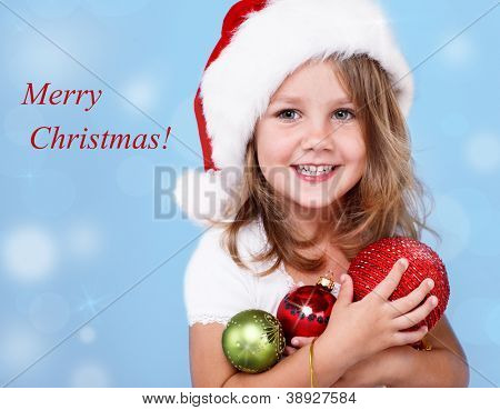 Happy preschool girl in Santa hat holding Christmas decoration in hands