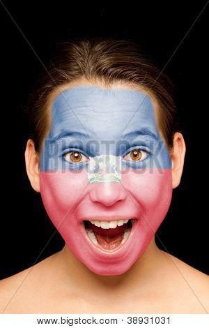 portrait of girl with haitian flag painted on her face