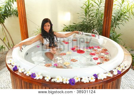 Pretty woman relaxing in jacuzzi with flower petals
