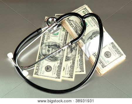 Healthcare cost concept: stethoscope and dollars on gray background