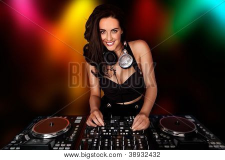 Beautiful busty DJ smiling at the camera with her headphones around her neck standing at her deck mixing sound in a nightclub or disco with coloured party lights behind her