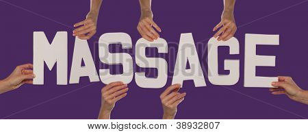 White alphabet lettering spelling MASSAGE held up over a purple studio background by outstreched female hands
