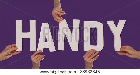 White alphabet lettering spelling HANDY held up over a purple studio background by outstreched female hands
