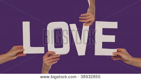 White alphabet lettering spelling LOVE held up over a purple studio background by outstreched female hands