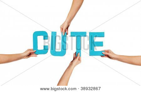 Turquoise blue alphabet lettering spelling CUTE held up over an isolated white background by outstretched female hands