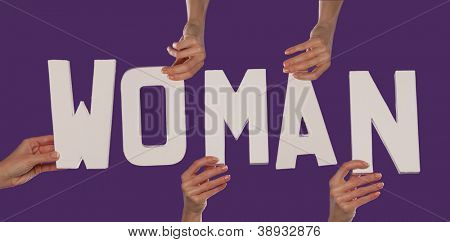 White alphabet lettering spelling WOMAN held up over a purple background by female hands