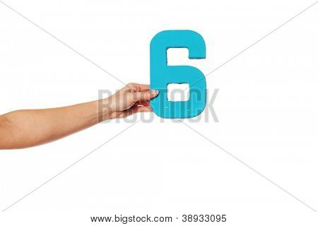Female hand holding up the number 6 against a white background conceptual of numbers, measurement, amount, quantity, accounting and mathematics