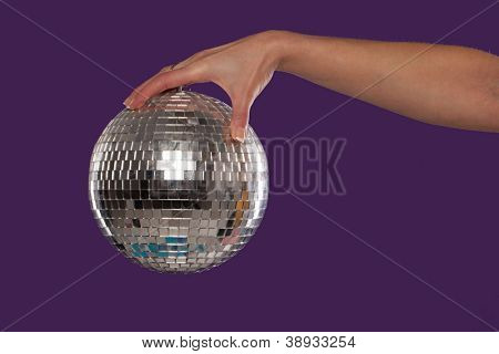 Female hand holding a suspended shiny silver mirrored disco ball over a purple studio background