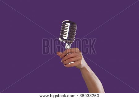 Female hand holding up a microphone over a purple studio background
