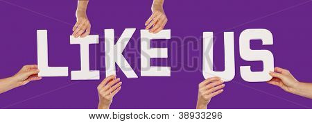 Female hands holding the text word for LIKE US in white capital letters isolated on a purple studio background