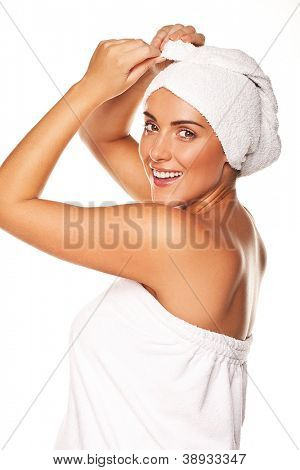 Beautiful woman tying up her wet hair in a towel after bathing in a fresh clean conceptual image for health and beauty isolated on white