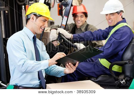 Supervisor de macho feliz comunicando-se com o motorista de empilhadeira e foreman no armazém