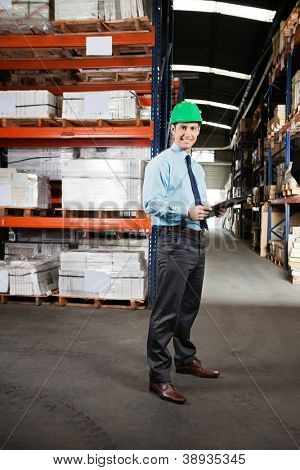 Portrait of confident young supervisor with clipboard standing at warehouse