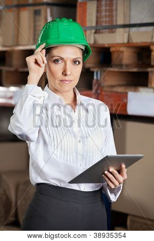 Portrait of confident young female supervisor with digital tablet standing at warehouse