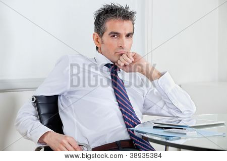 Portrait of mid adult businessman with digital tablet relaxing at desk in office
