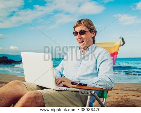 Business man sitting and working on the beach working on mobile computer