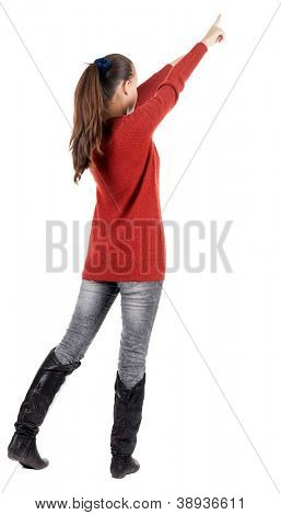 Back view of young brunette woman pointing at wall . beautiful girl in red sweater. Rear view people collection.  backside view of person.  Isolated over white background.
