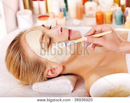 Mujer con máscara facial de arcilla en el spa de belleza.