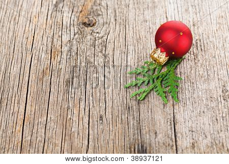 Red Christmas ball on wooden background with green thuja branch